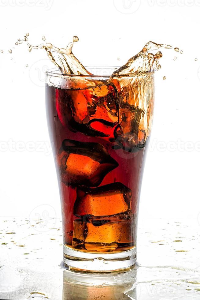Eiswürfel fiel in Cola-Glas und spritzte foto