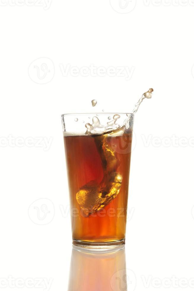 Eiswürfel fällt in ein Glas Cola foto
