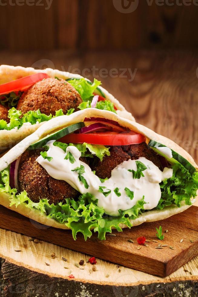 Falafel und frisches Gemüse im Fladenbrot auf Holztisch foto