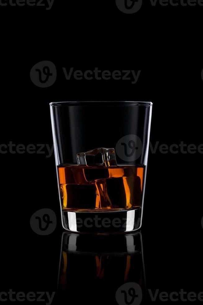 Glas mit Whisky und Eis auf Schwarz foto