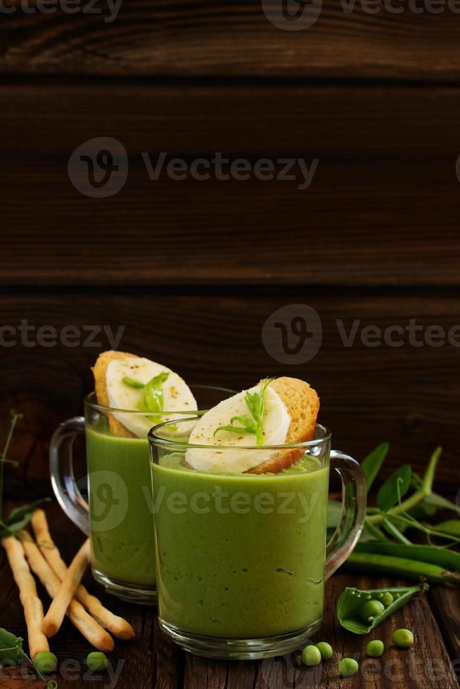 grüne Erbsensuppe mit Croutons und Käse. foto