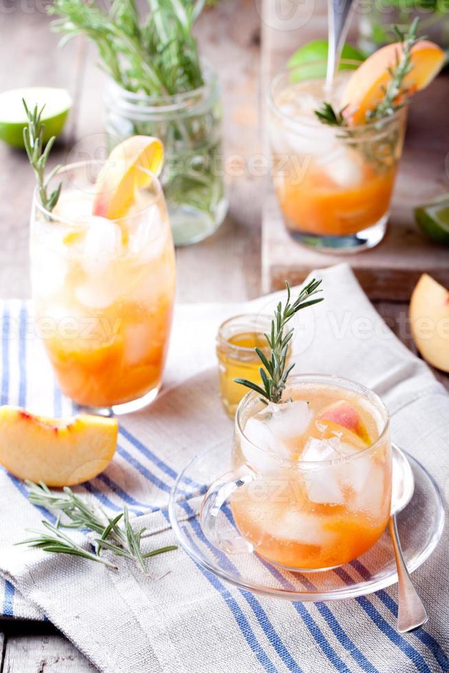 Pfirsich-Rosmarin-Fizz-Cocktail auf einem hölzernen Hintergrund. Cocktail. foto