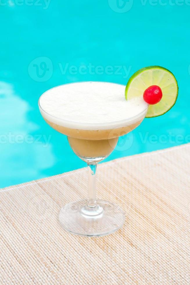 Strandblond Cocktail in der Nähe von Wasserpool auf der Matte foto