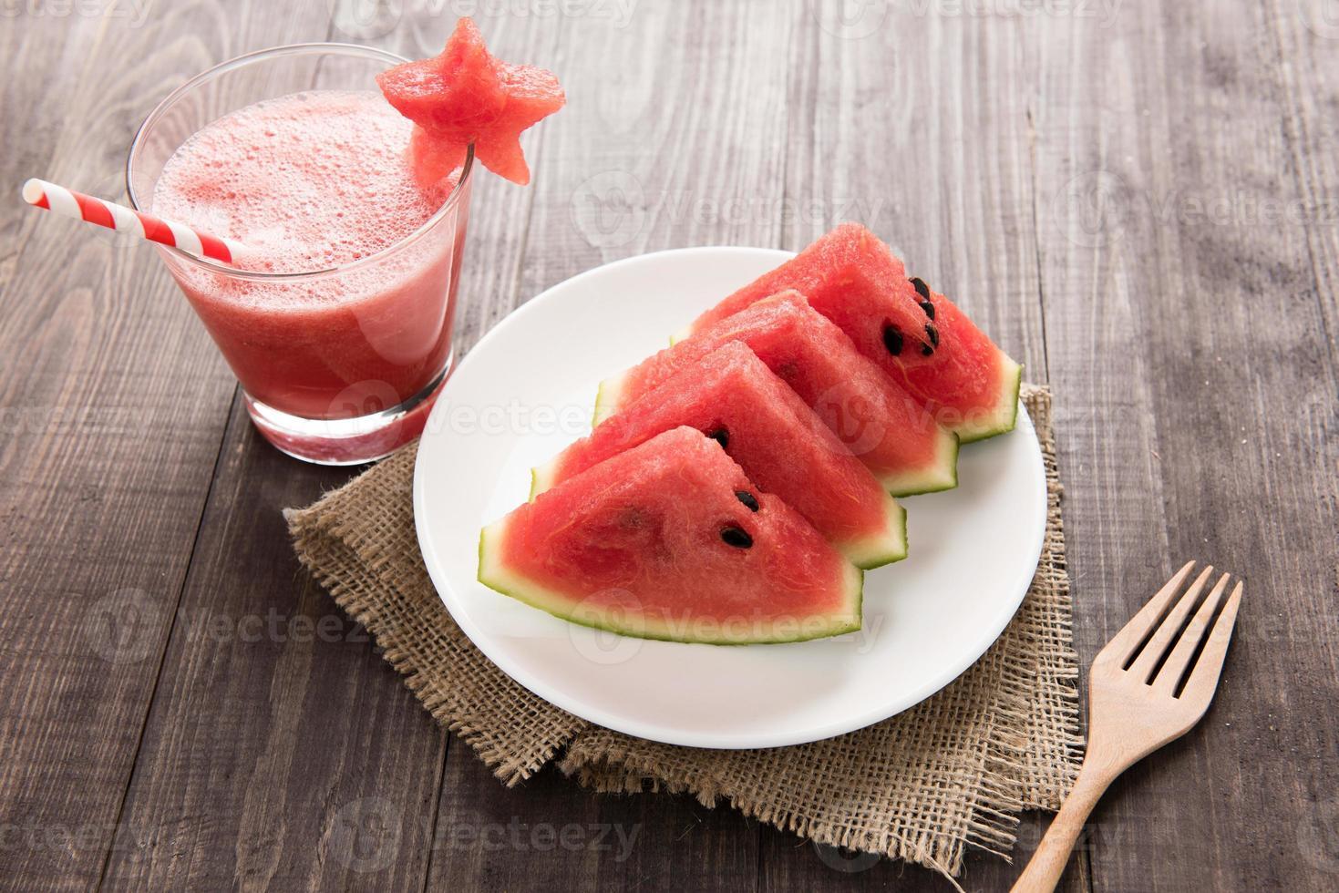 gesunde Scheibe Wassermelone mit Wassermelonen-Smoothie auf einem Holzrücken foto
