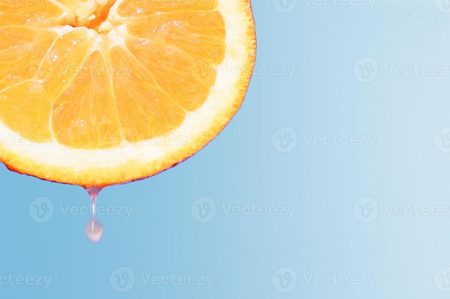 Orangenhälfte mit tropfendem Saft foto