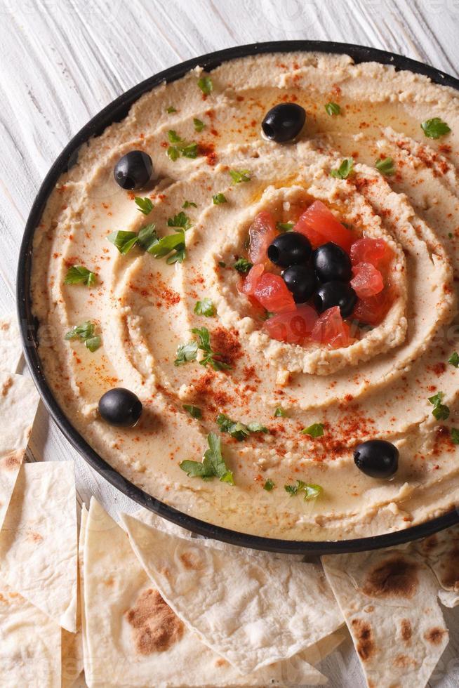 Hummus mit Oliven und Kräutern auf einer Teller-Nahaufnahme. Vertikale foto