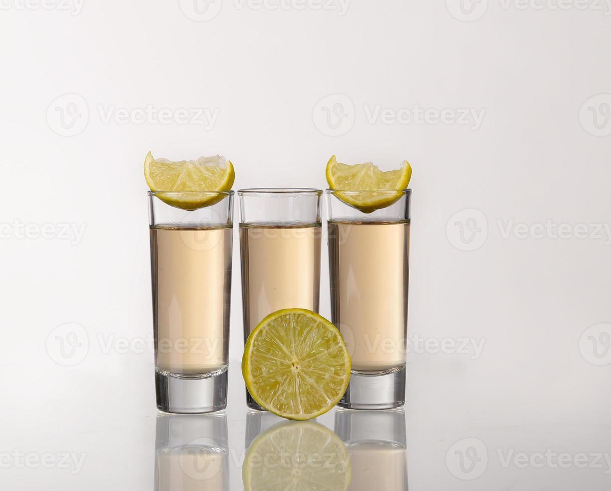 drei goldene Tequila-Aufnahmen mit Limette auf weißem Hintergrund foto