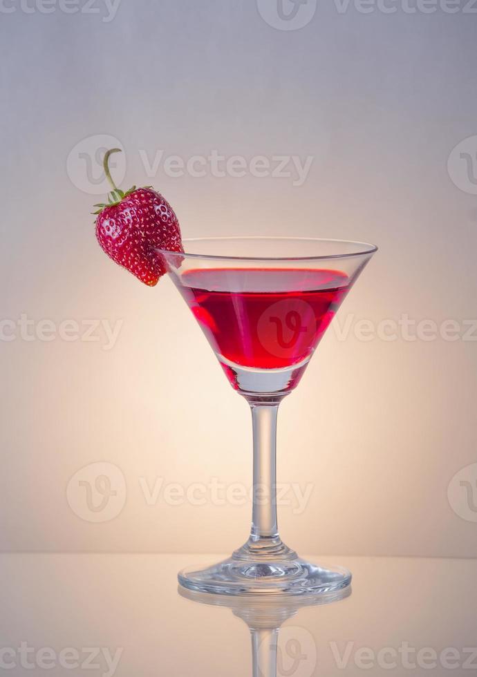 roter Cocktail garniert mit Erdbeere in einem Martini-Glas foto