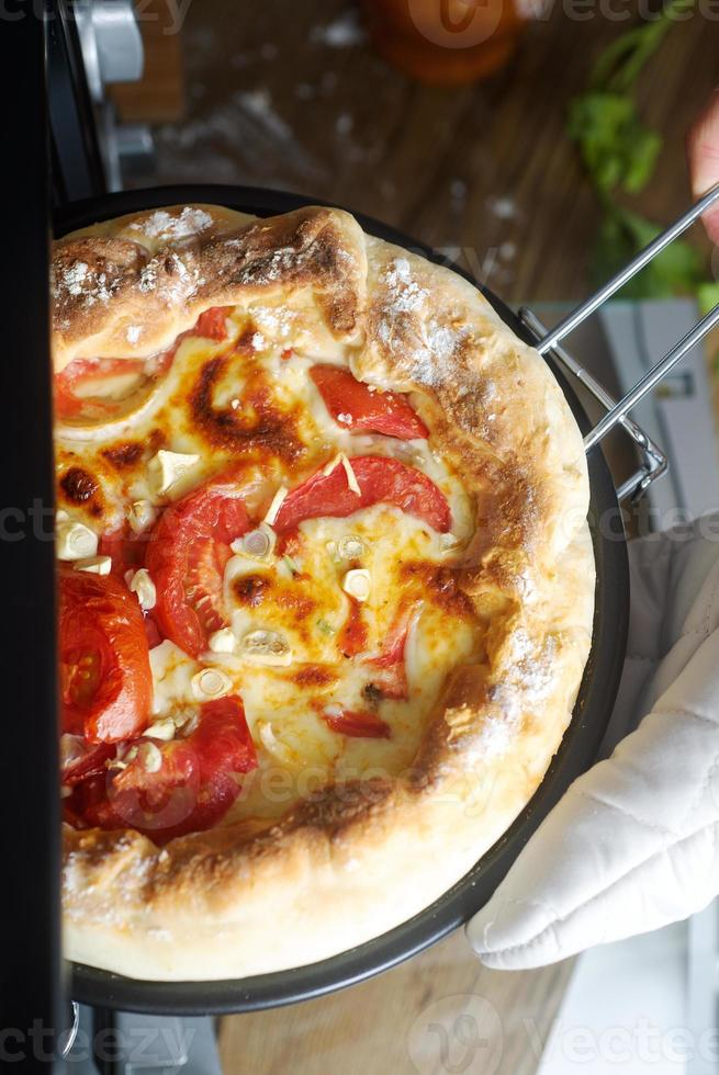 Koch nehmen fertige Margarita-Pizza vom Herd foto