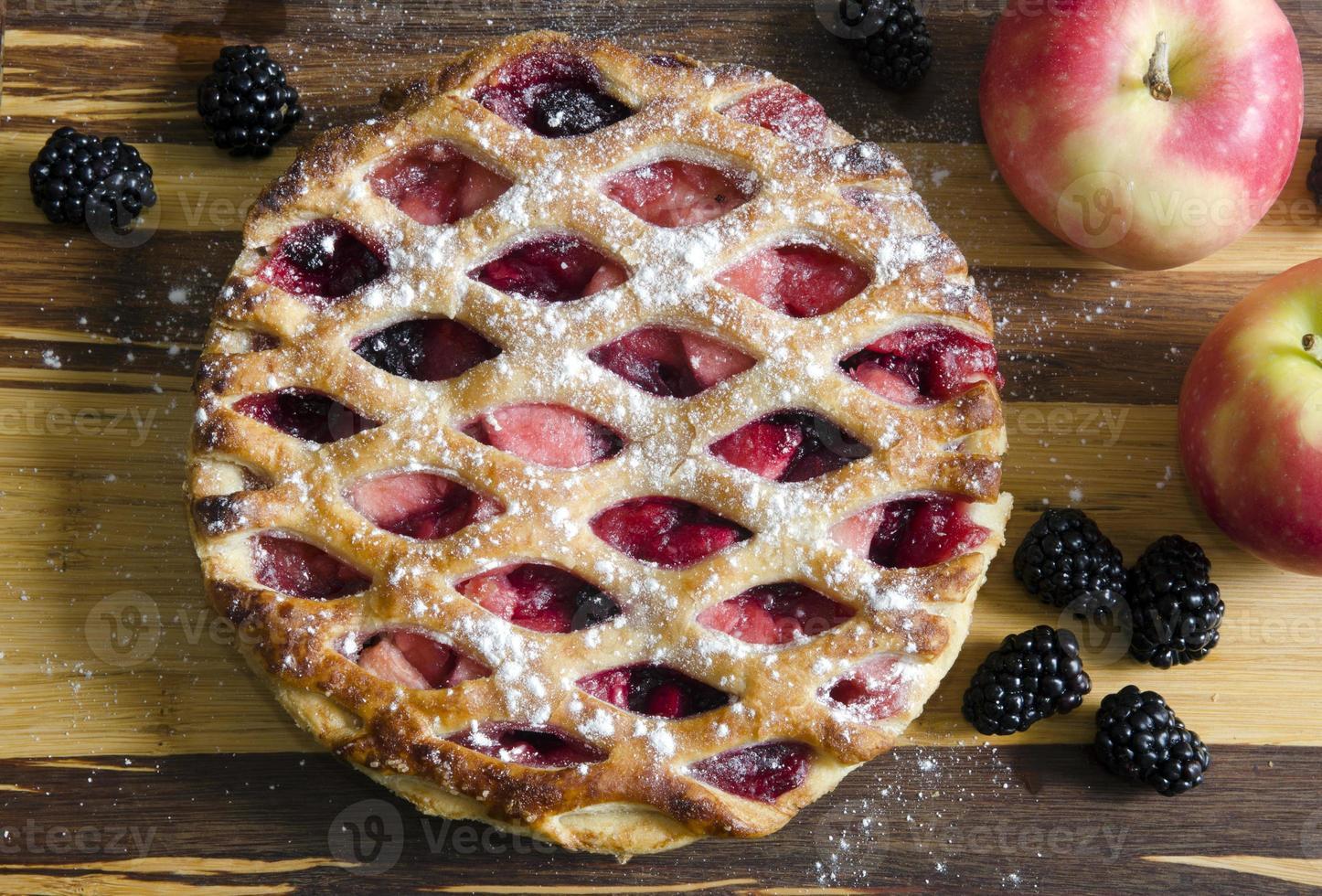 Apfelkuchen mit Beeren auf Holztisch foto