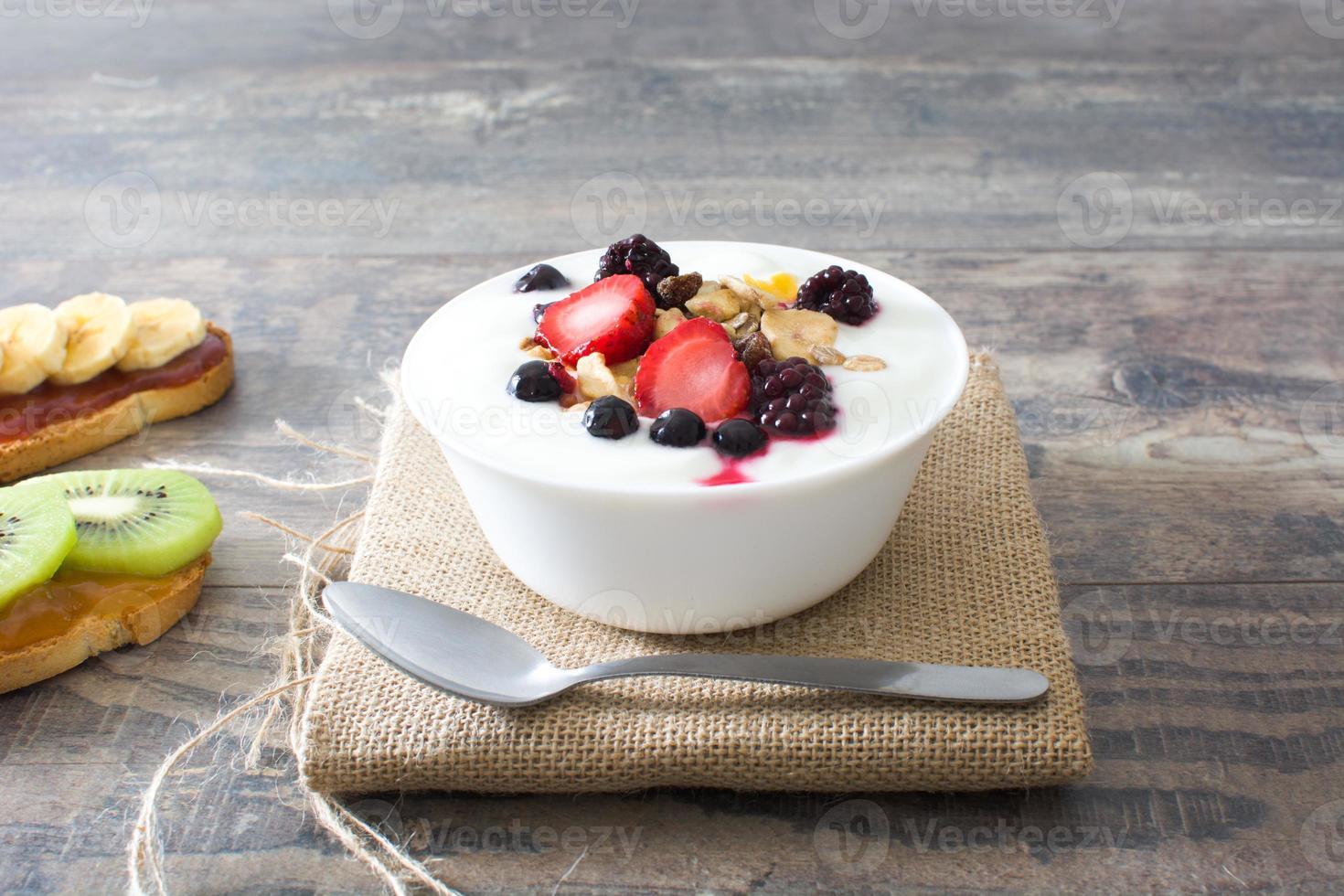 Naturjoghurt mit frischen Beeren und mit Obst geröstet foto