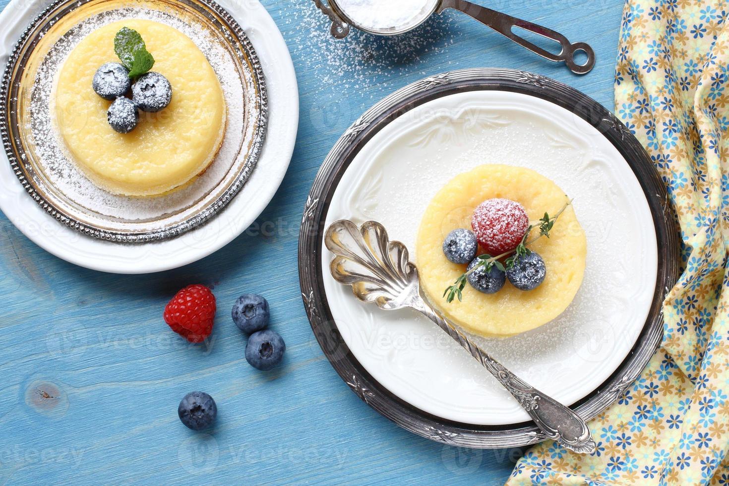 Zitronenüberraschungspuddingkuchen mit Beeren serviert foto