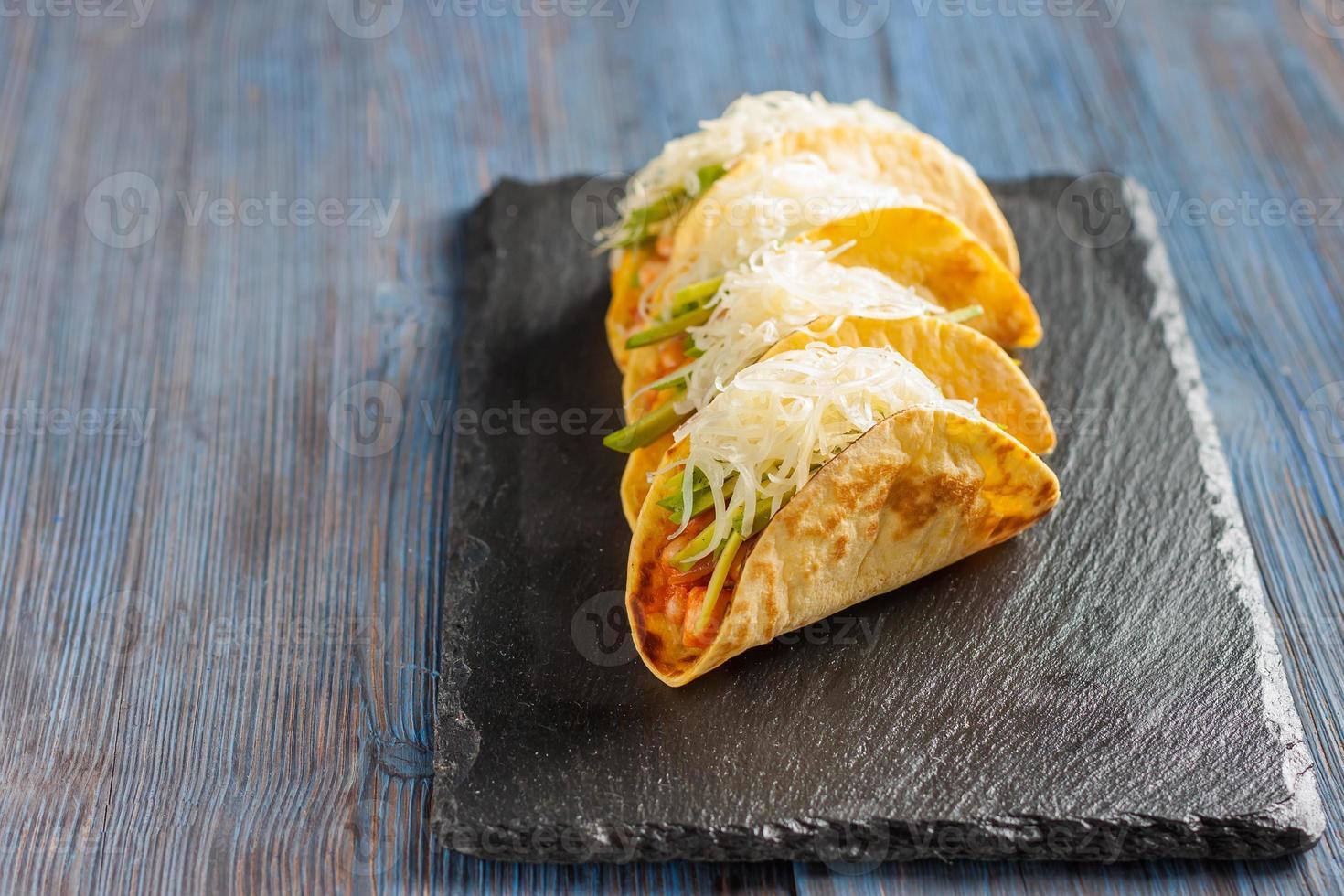 mexikanische Tacos mit Fleisch, Bohnen, Avocado, Käse und Tomatensauce foto