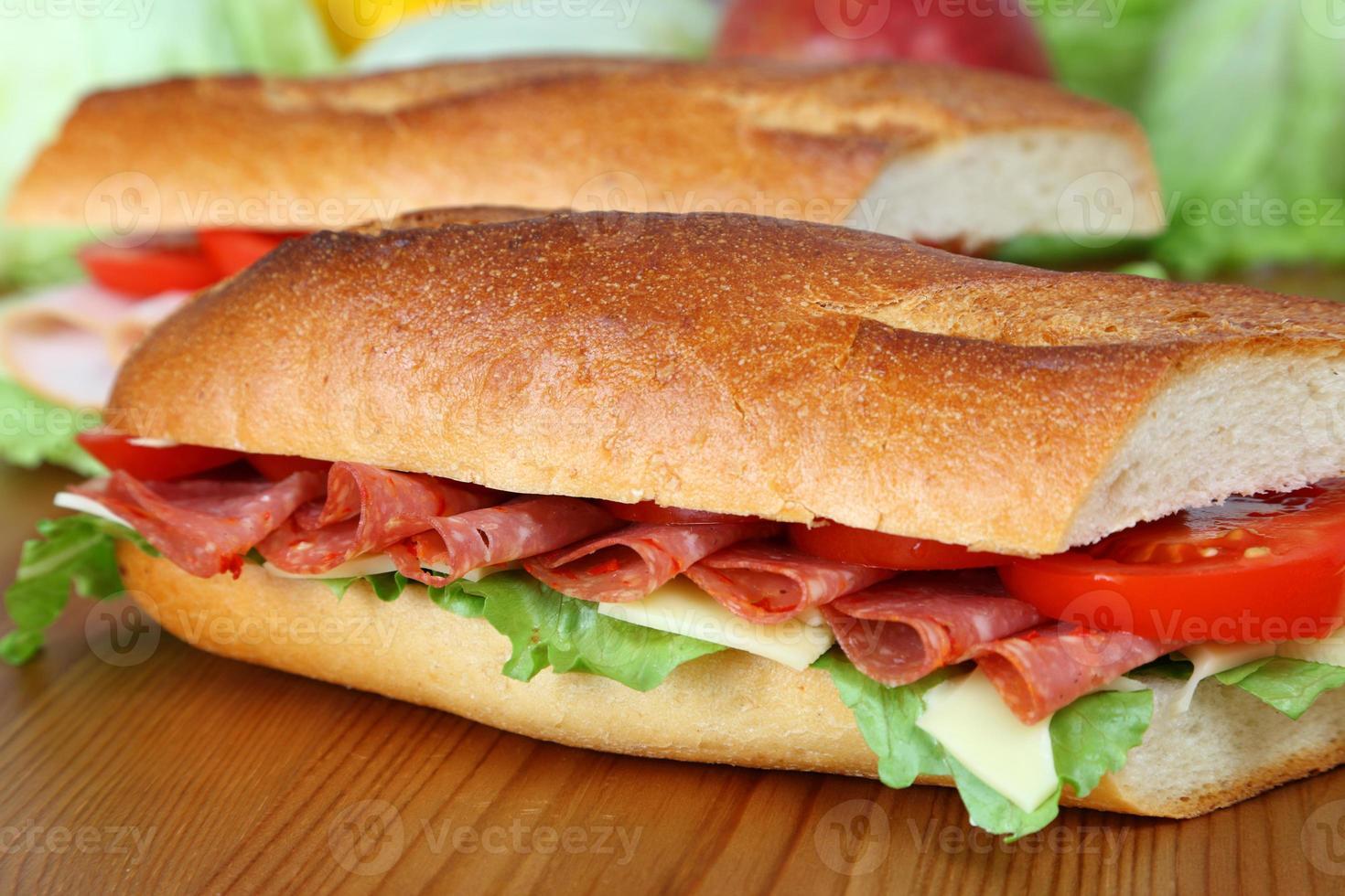 Salamisandwich mit Salat, Käsescheiben und Tomaten foto