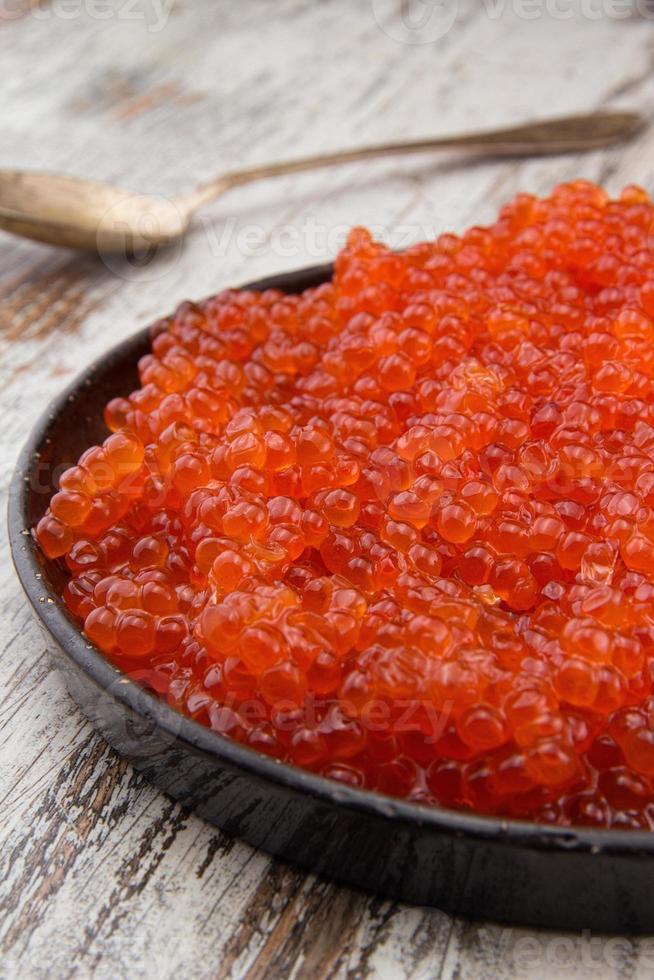 roter Kaviar in einer schwarzen Platte über einem Weinlesehintergrund foto