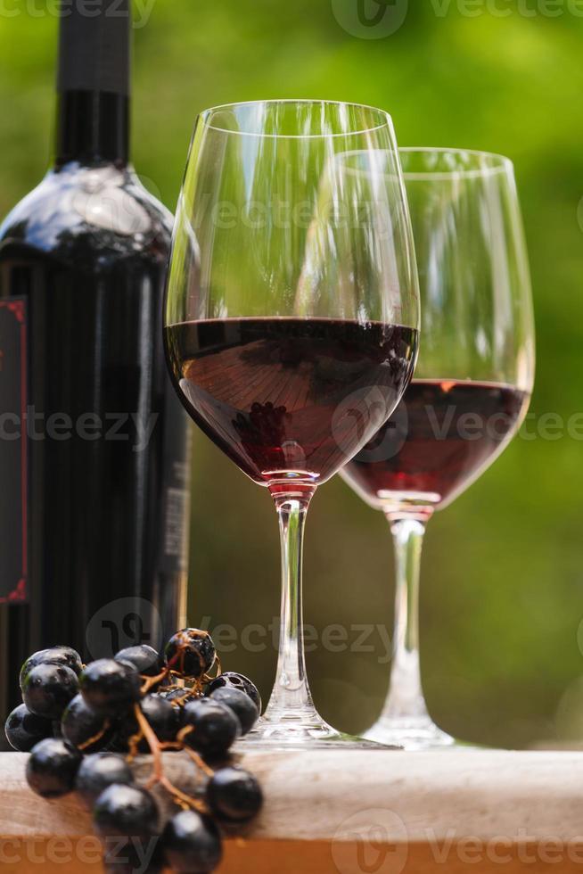 Flasche mit zwei Weingläsern und Weintraube foto