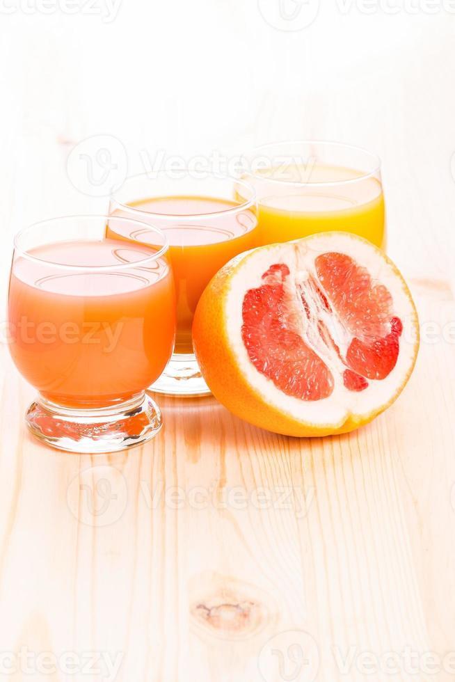 drei Gläser Saft mit halbierter Grapefruit foto