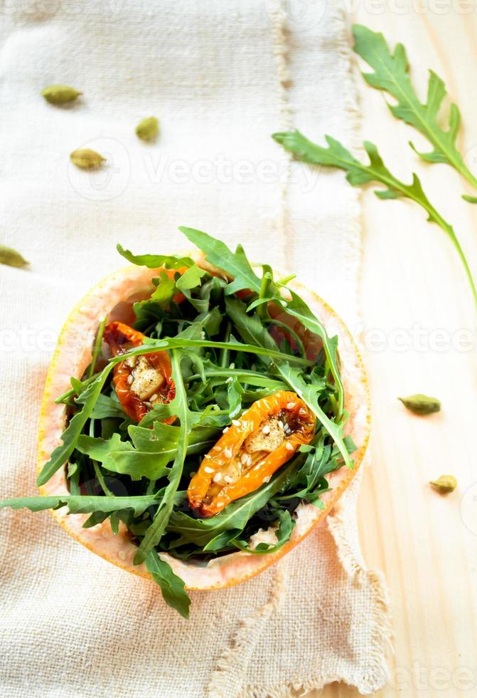 Salat mit Rucola, sonnengetrockneten Tomaten und Sesam in Grapefruit foto