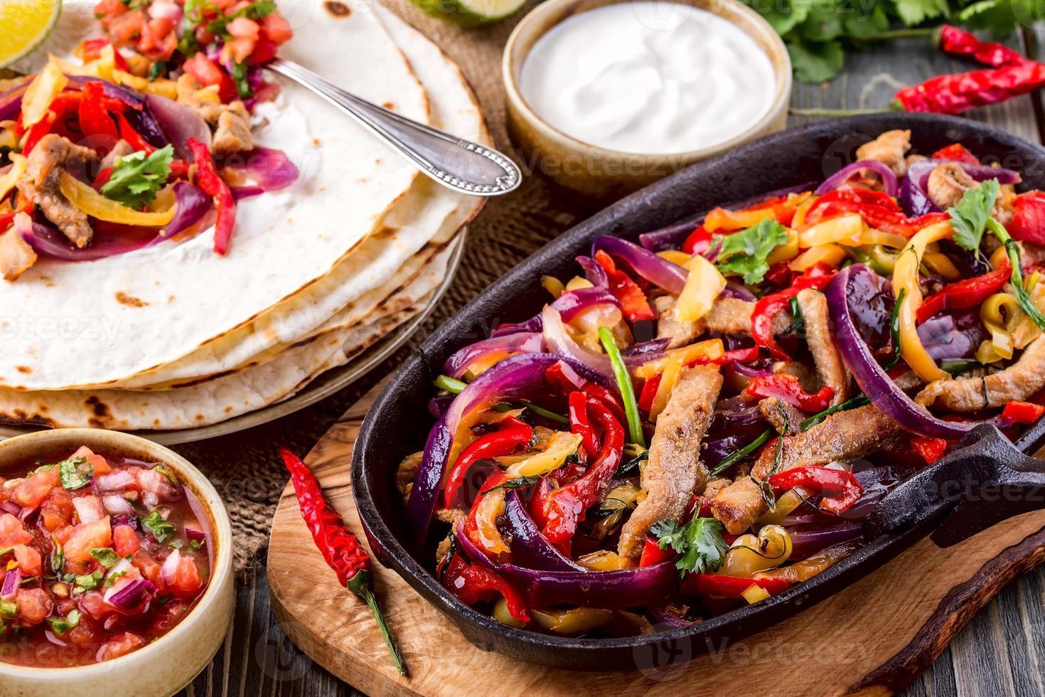 Schweinefleisch-Fajitas mit Zwiebeln und farbigem Pfeffer, serviert mit Tortill foto