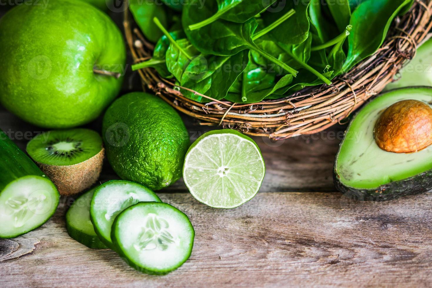 Mischung aus grünem Obst und Gemüse auf rustikalem Holzhintergrund foto