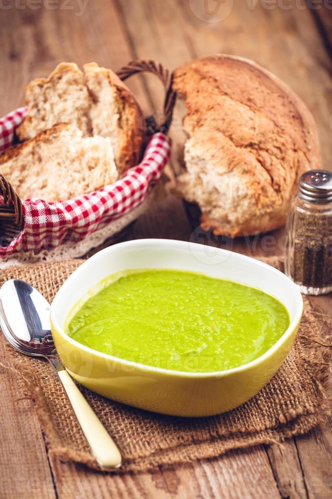 grüne Erbsensuppe in Schüssel mit Brot und Sauerrahm foto