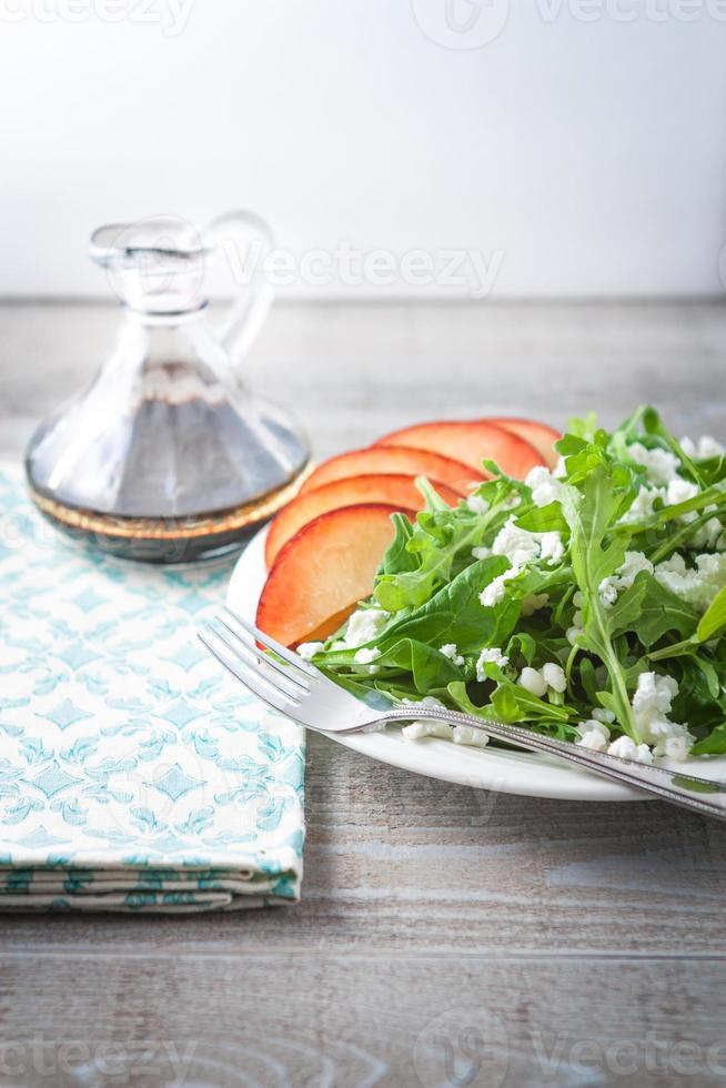 frischer Rucola-Spinat-Salat mit Nektarine auf dem Tisch foto