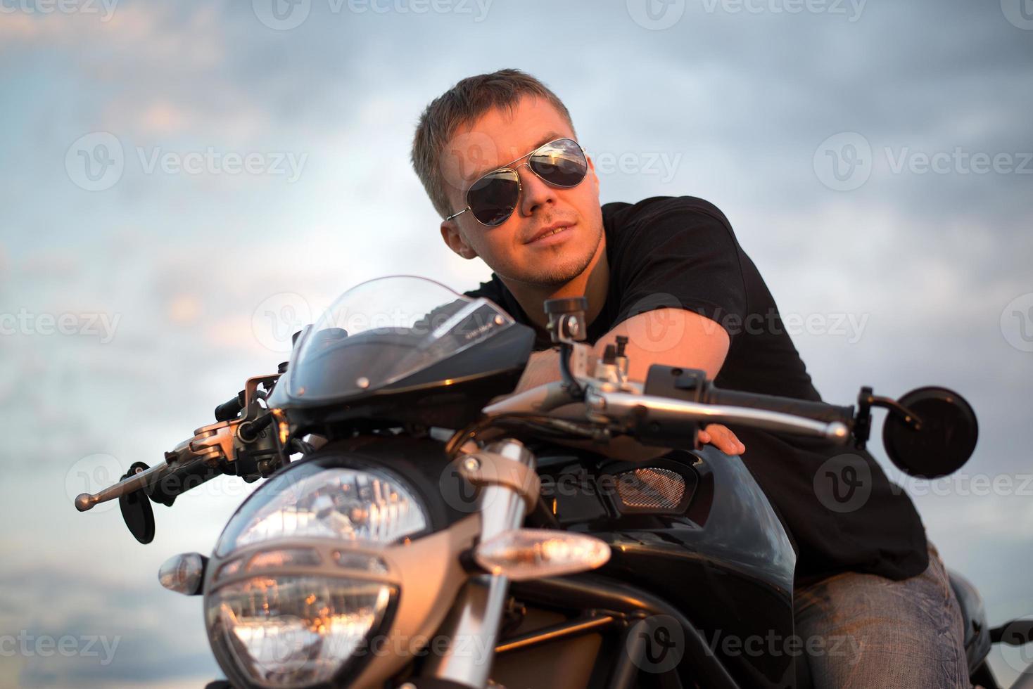 romantischer Porträt schöner Biker Mann sitzt auf einem Fahrrad foto