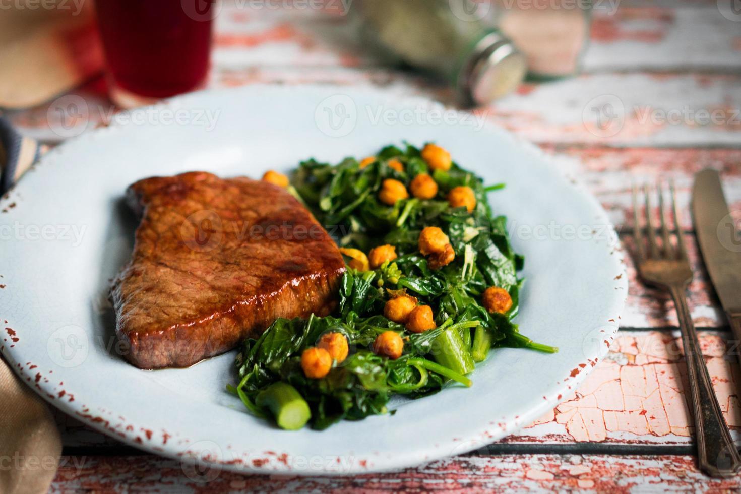 frisches Steak mit grünem Salat auf rustikalem Holzhintergrund foto