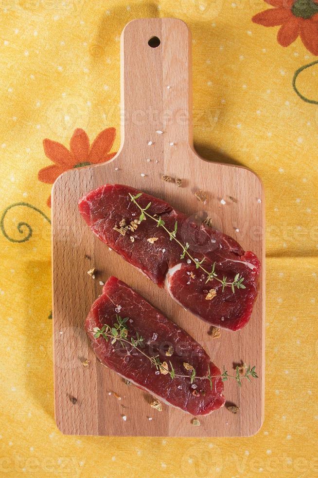 rohes Rinderfilet mit Gewürzen über Holztisch foto