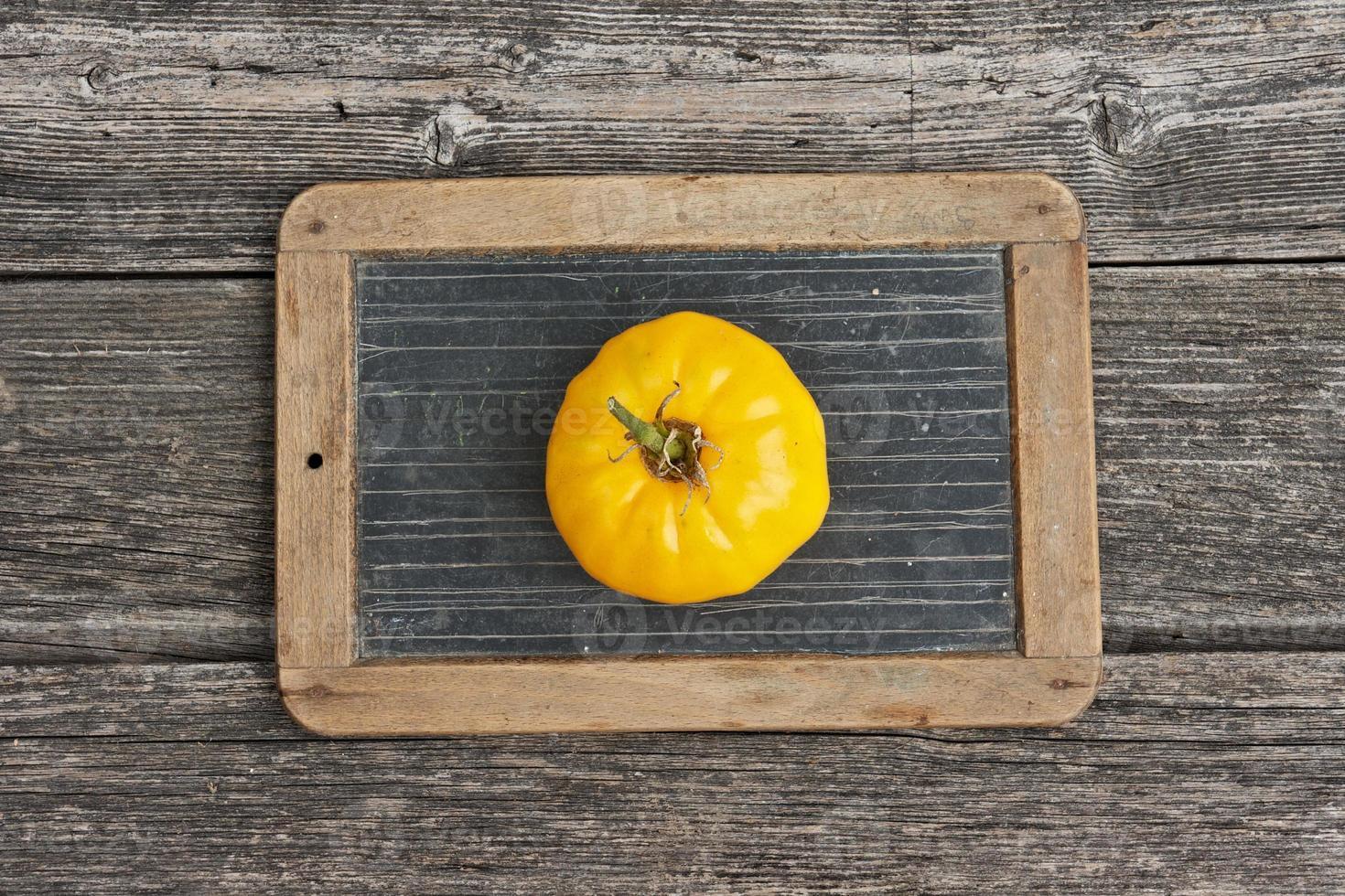 Tomate auf der Schieferschreibtafel foto