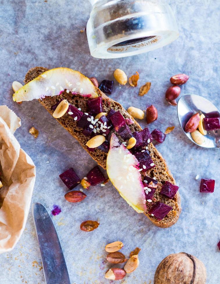 Sandwich mit gerösteten Rüben, Nüssen, Birnen und Sesam foto