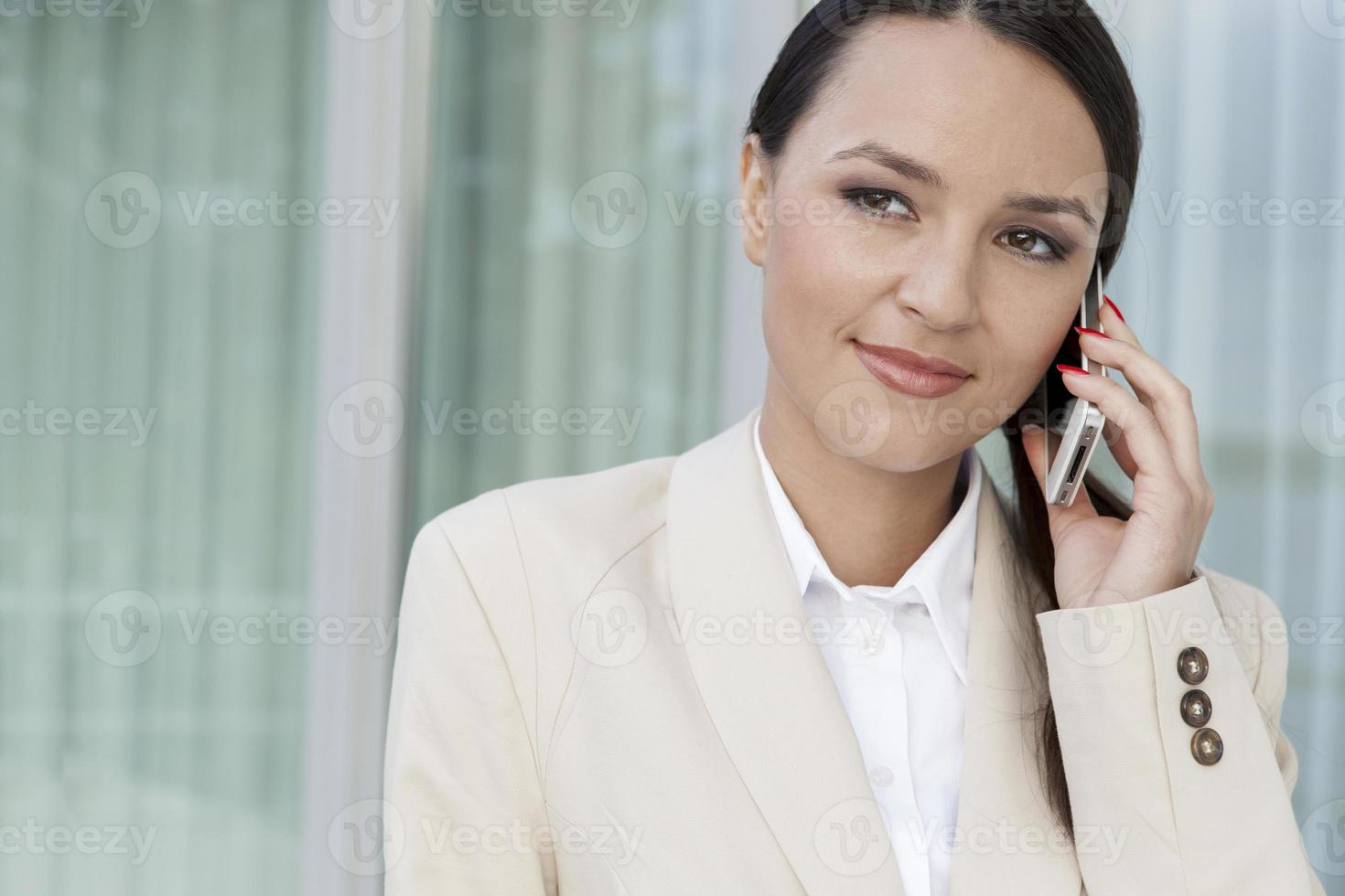 schöne Geschäftsfrau, die Handy im Freien beantwortet foto