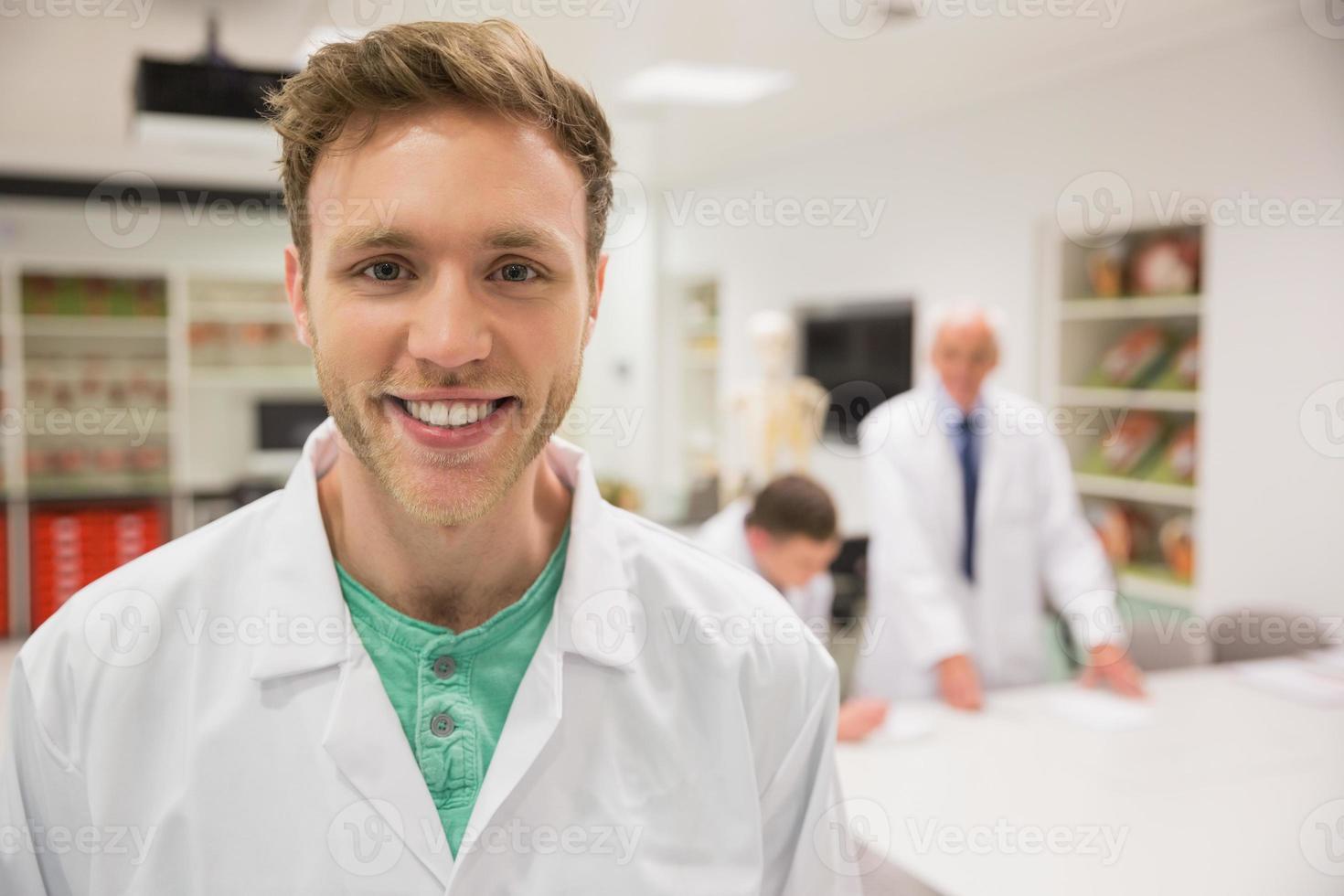 hübscher Wissenschaftsstudent, der in die Kamera lächelt foto