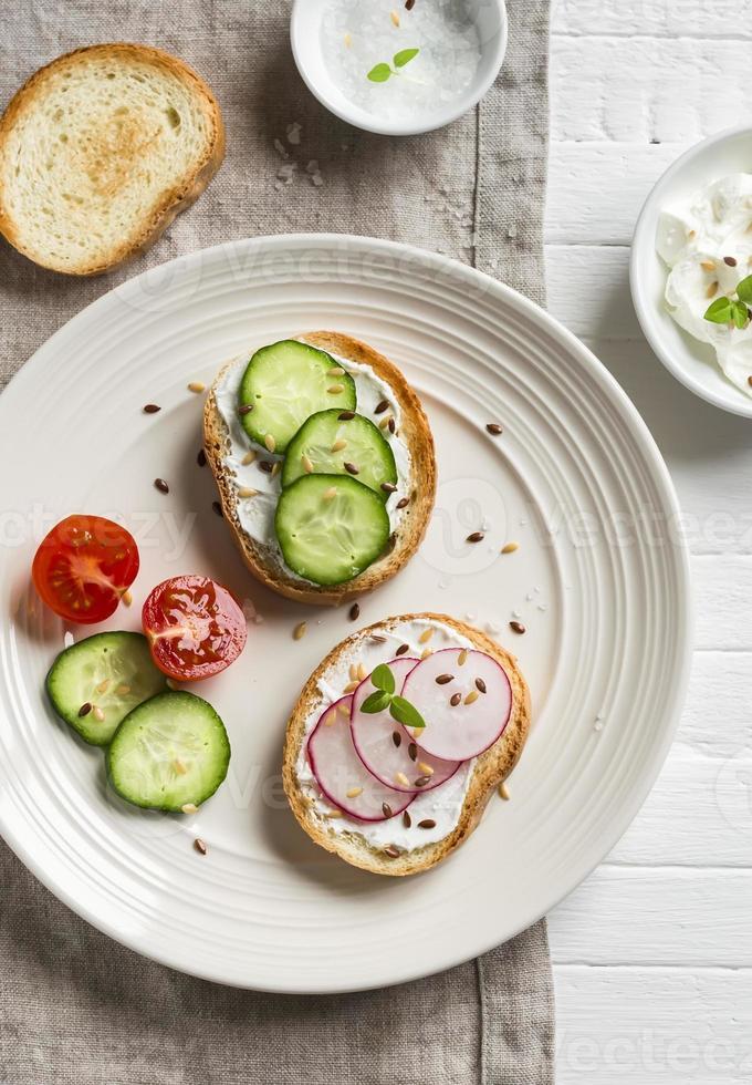 Sandwiches mit Frischkäse, Gurke und Radieschen auf leichtem Teller foto