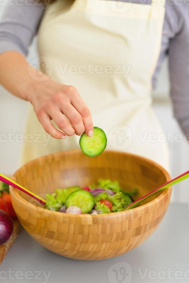 Nahaufnahme auf junge Frau, die Gurke im Salat hinzufügt foto