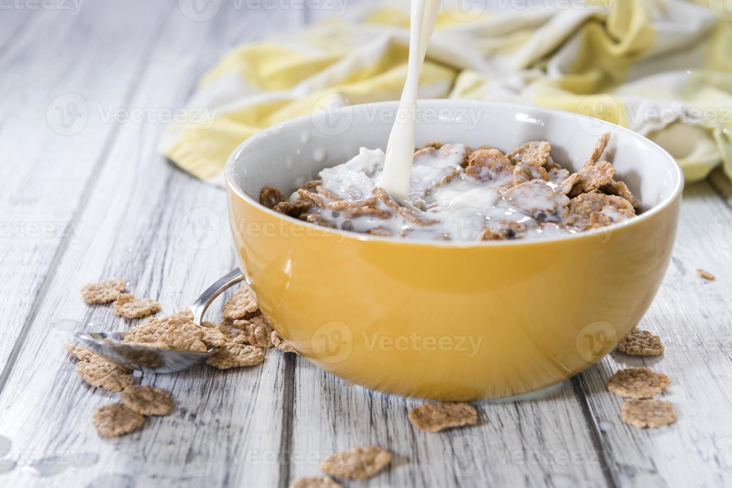 Milch in eine Schüssel mit Cornflakes gießen foto