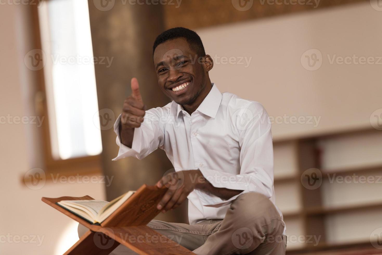 Schwarzafrikanischer muslimischer Mann, der Daumen oben zeigt foto