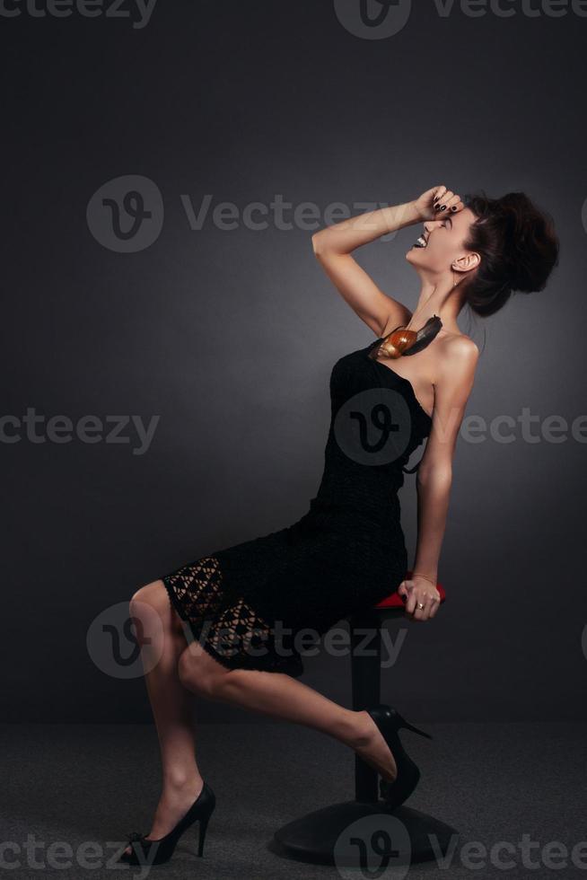 Frau mit Schnecke im schwarzen Kleid lachend. Mode. gotisch foto