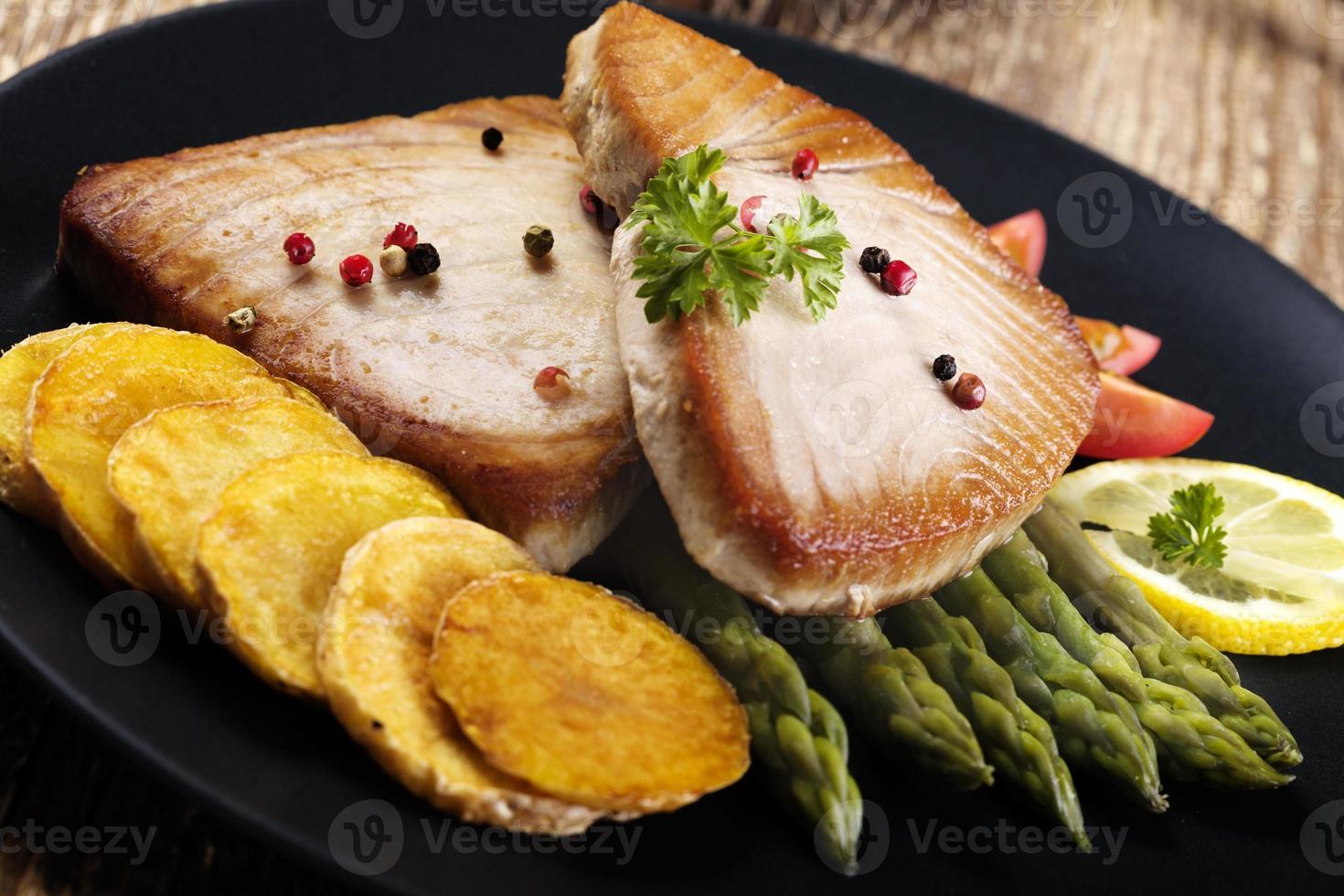 Gegrilltes Thunfischsteak auf Spargel mit geröstetem Zmieniakami foto