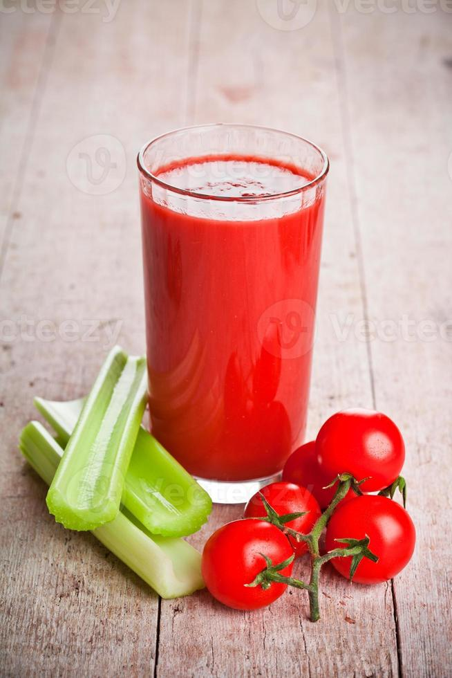 Tomatensaft in Glas, frischen Tomaten und grünem Sellerie foto