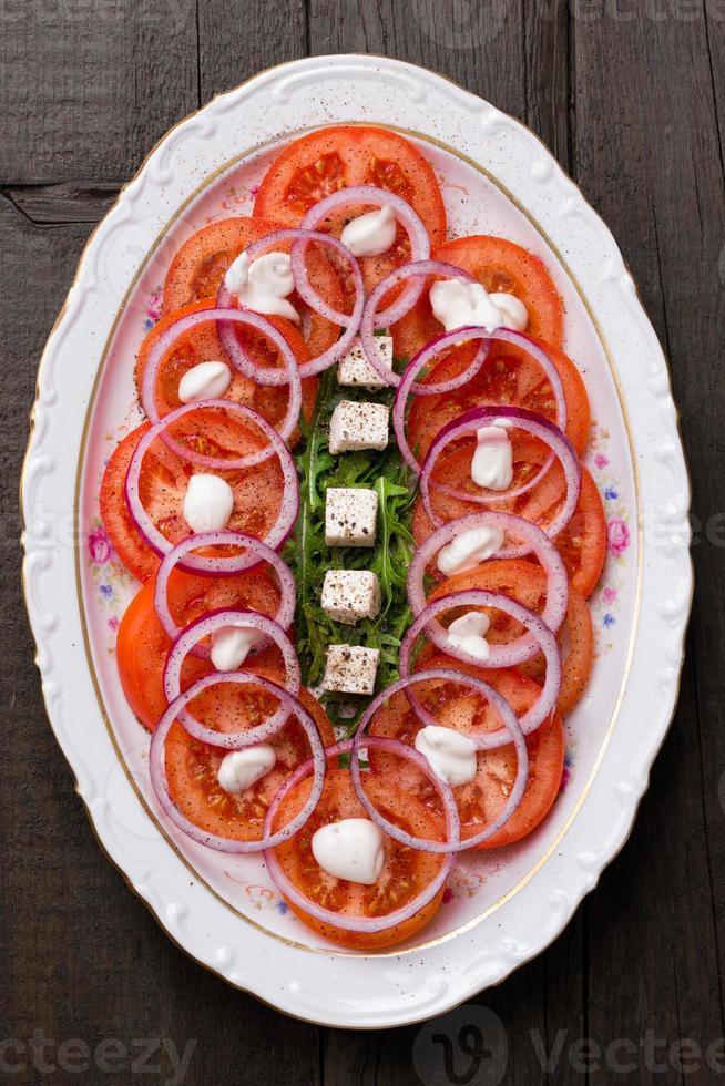 Tomaten-, Feta-, Zwiebel- und Rucola-Salat foto