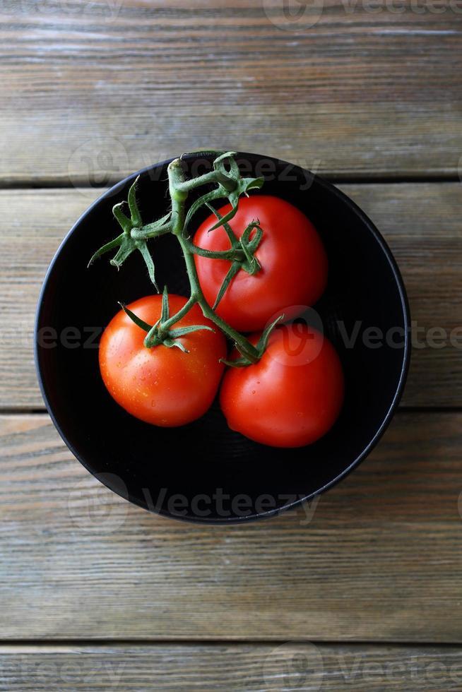 rote Tomaten in schwarzer Schüssel foto