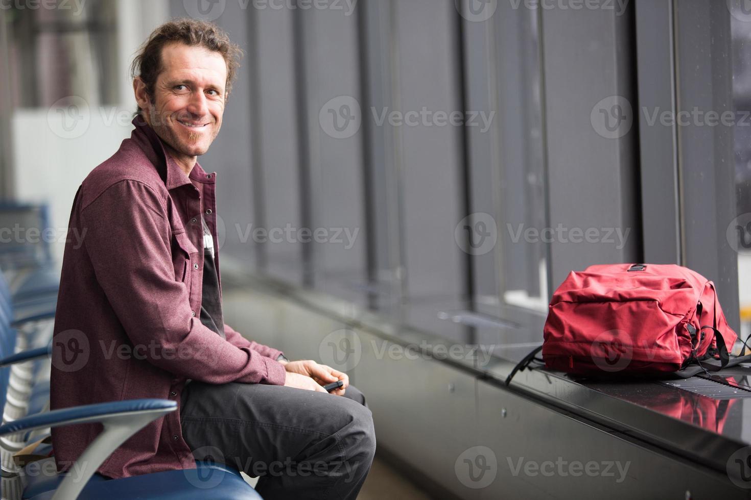Mann wartet auf Flug am Flughafen foto
