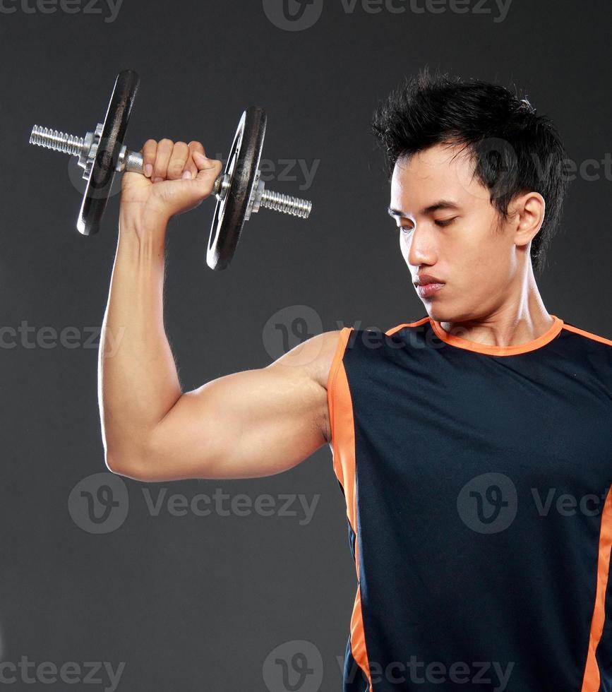 junger Mann, der mit Gewichtheben trainiert foto