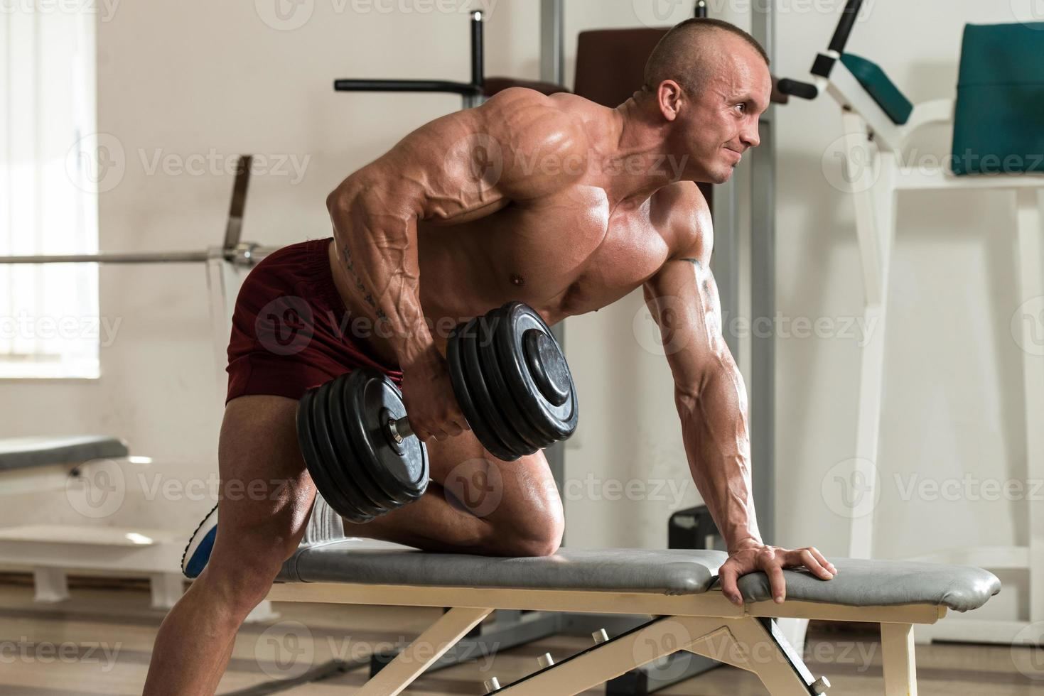 gesunder Mann, der Rückenübungen mit Hantel macht foto