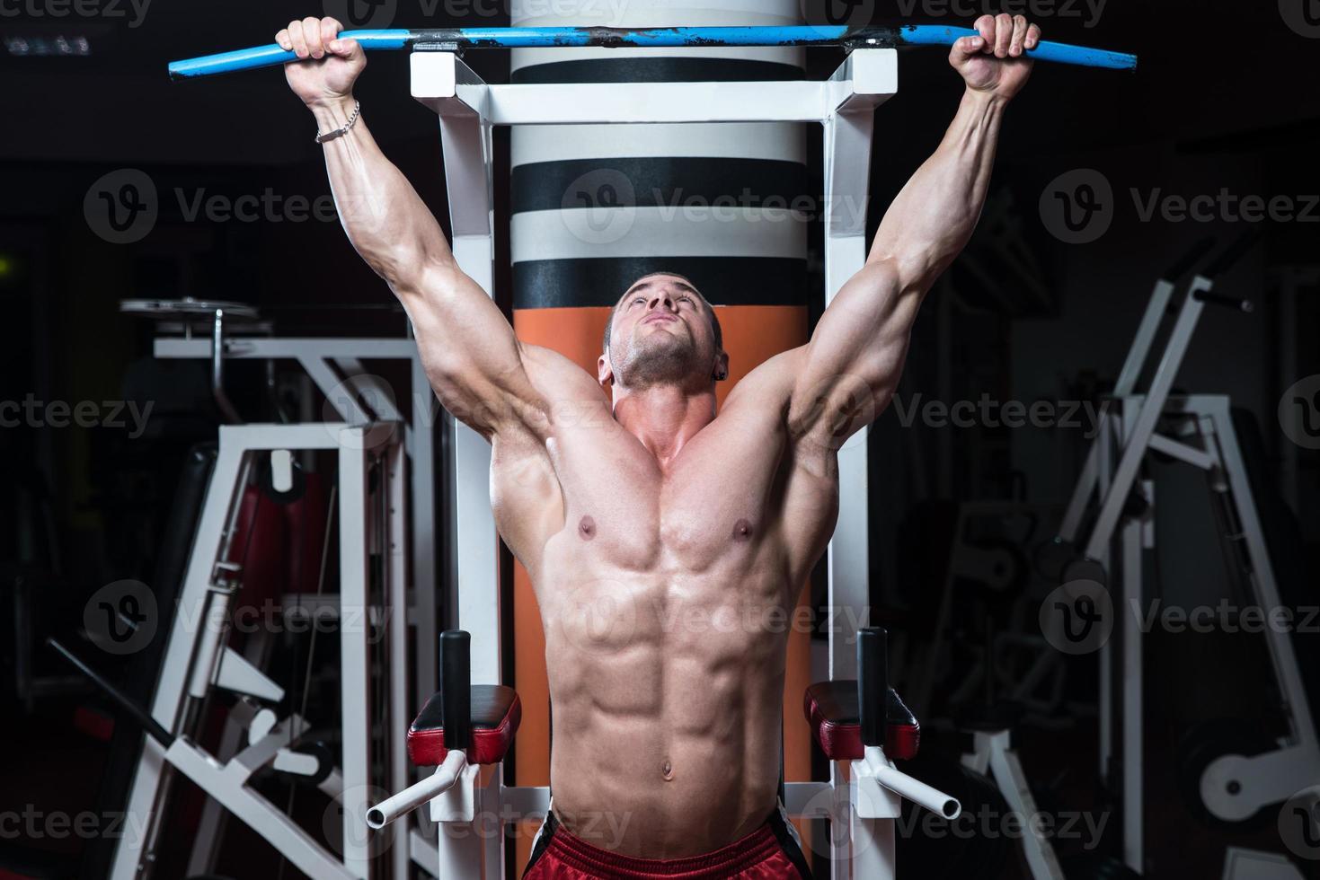 junger Bodybuilder, der schwere Gewichtsübungen für den Rücken macht foto