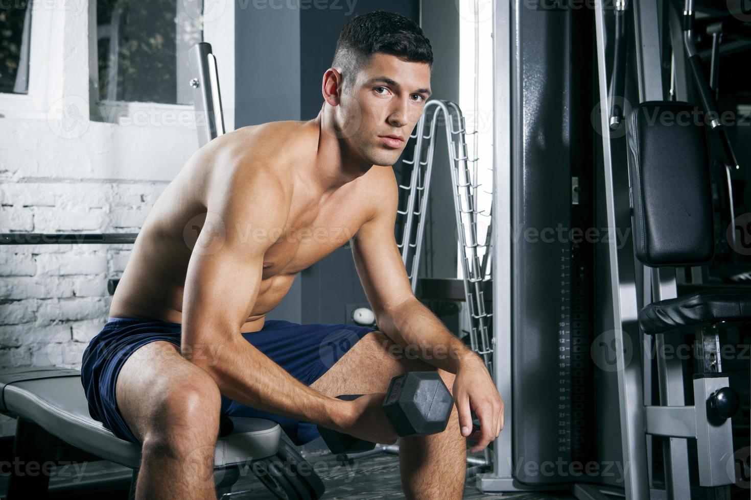 muskulöser Mann, der mit Hanteln im Fitnessstudio trainiert foto