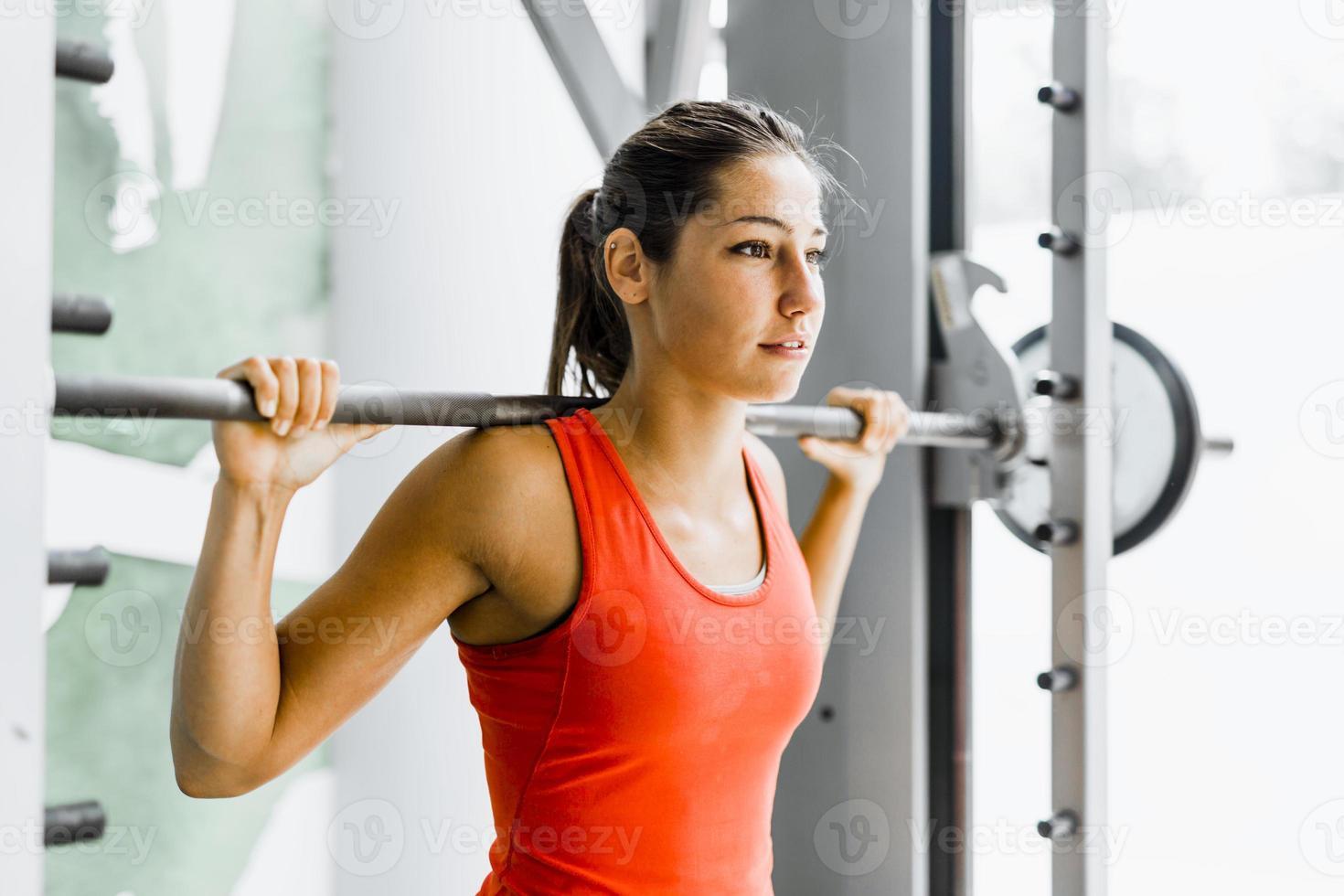 junge schöne Frau, die Gewichte in einem Fitnessstudio hebt foto