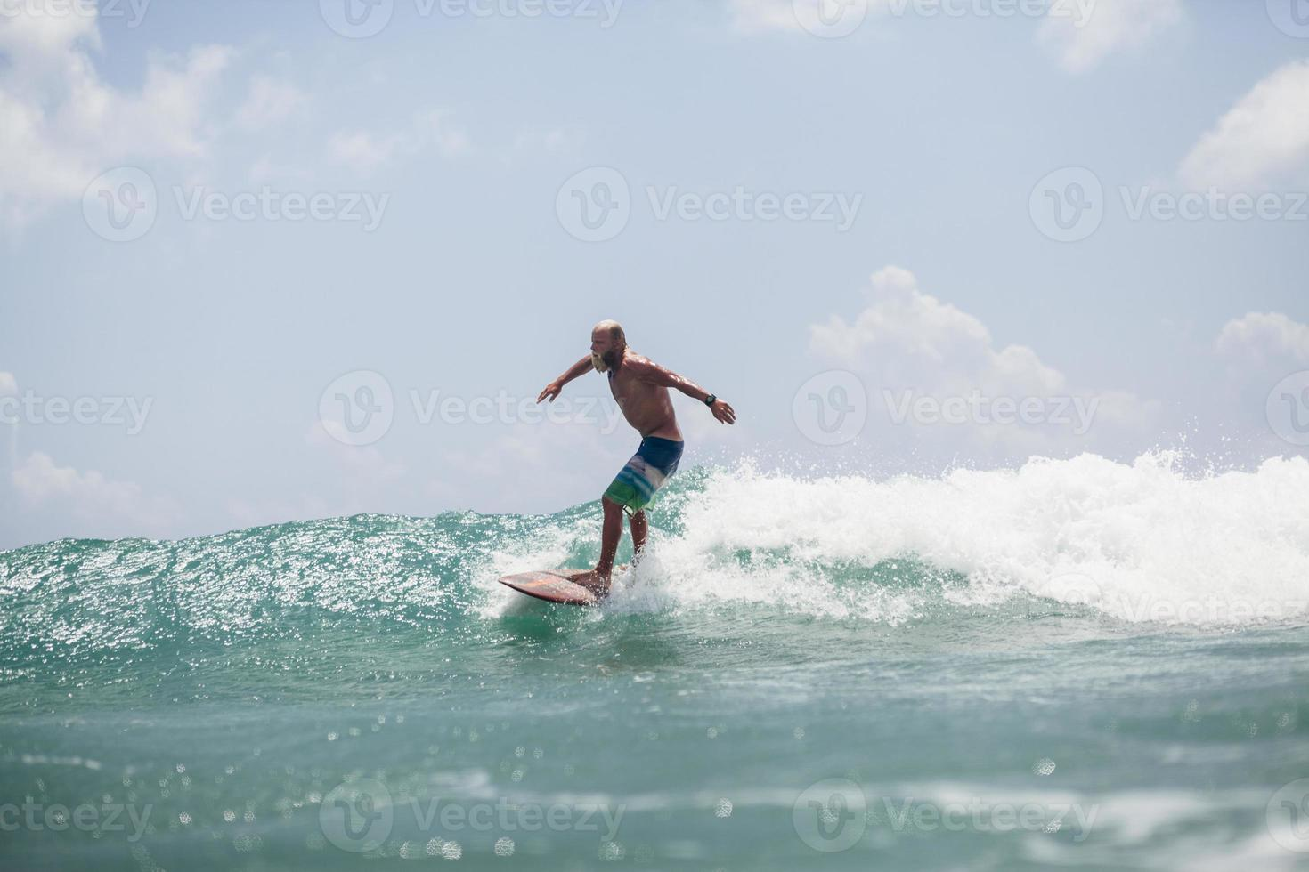 Surfer Mann, der auf Wellen surft, spritzt aktiv foto