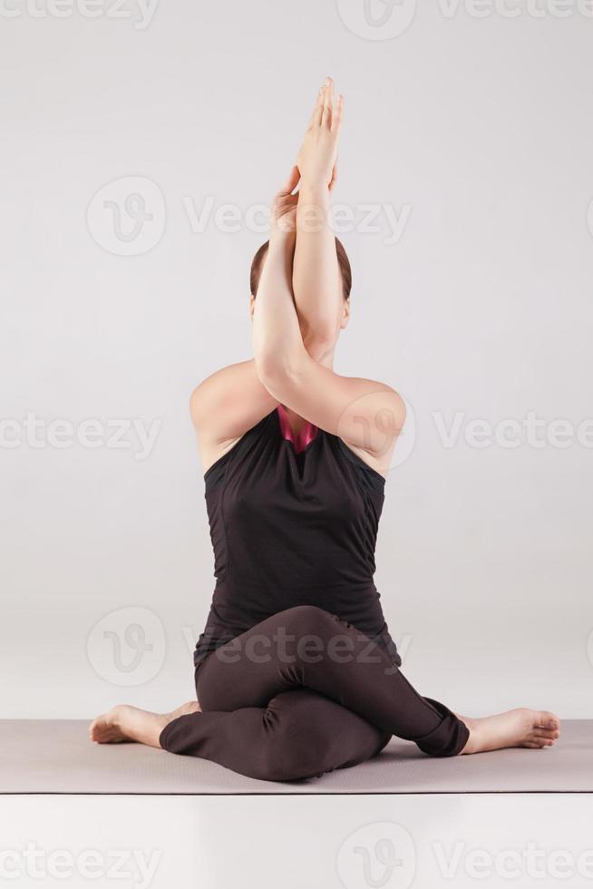 junges schönes Yoga, das auf grauem Hintergrund aufwirft foto